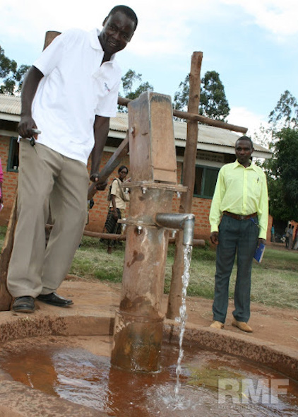 man pumping water from a well