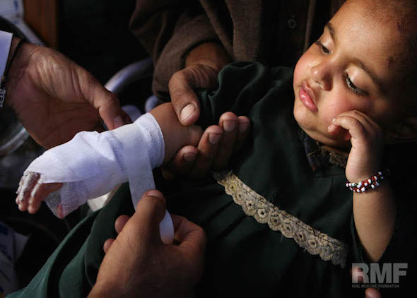 young child gets hand wrapped