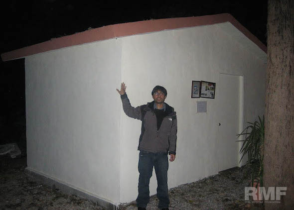man standing next to a building